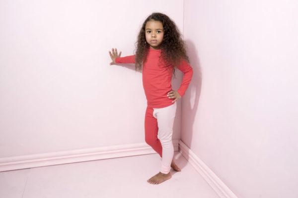 Ein Mädchen mit roten schönen Leggings von der Marke Gugguu