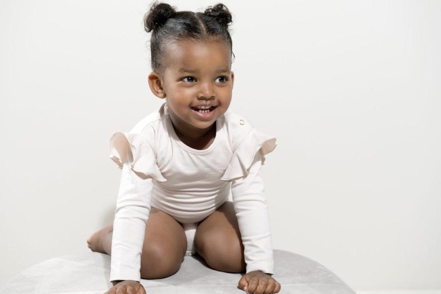 Ein Baby mit einem schneeweissem Body von Gugguu