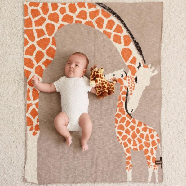 EIn Baby auf einem warmen und weichen Decke aus Biobaumwolle mit Giraffenmotiv von der Marke Quschel.