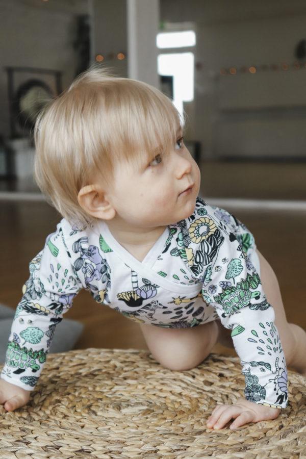 Ein Baby mit einem Wickelbody mit Regewaldmotiv von aarrekid