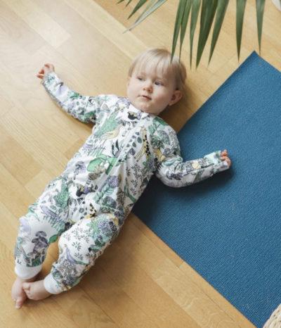 Ein Baby mit Strampler mit Regenwaldmotiv von der Marke Aarrekid