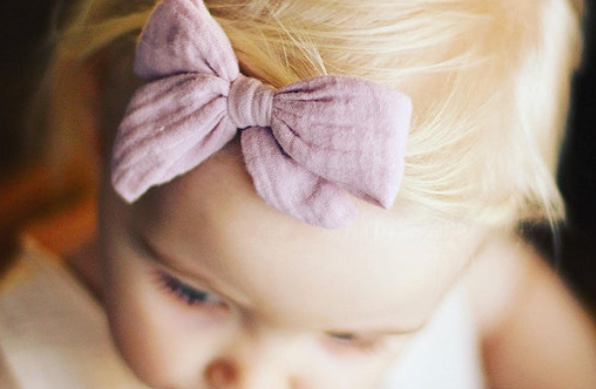 Ein Baby mit einem Haarband in violet