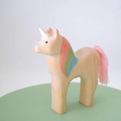 Ein Einhorn aus Holz mit einer regegenbogen farbene Mähe
