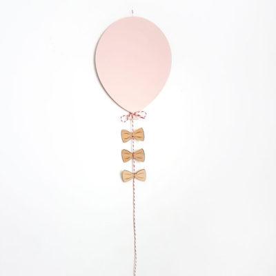 Ein Ballon aus Holz in Rosa an der Kinderzimmerwand